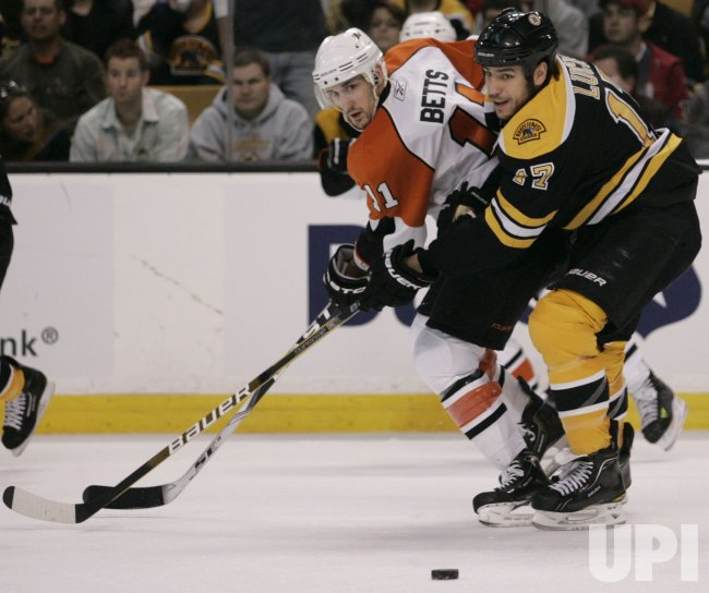 Bruins Lucic and Flyers Betts chase puck in Game 5 of the NHL Eastern Conference Semi-Final in Boston, MA.