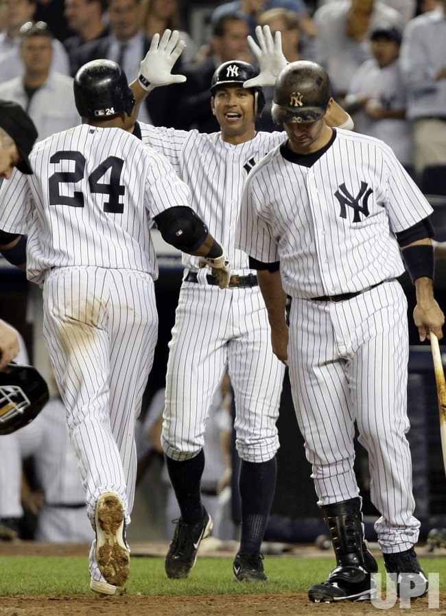 New York Yankees Alex Rodriguez reacts while Robinson Cano crosses home plate at Yankee Stadium in New York