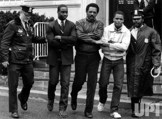 Jesse Jackson and his sons are arrested on the steps of the South African Embassy.