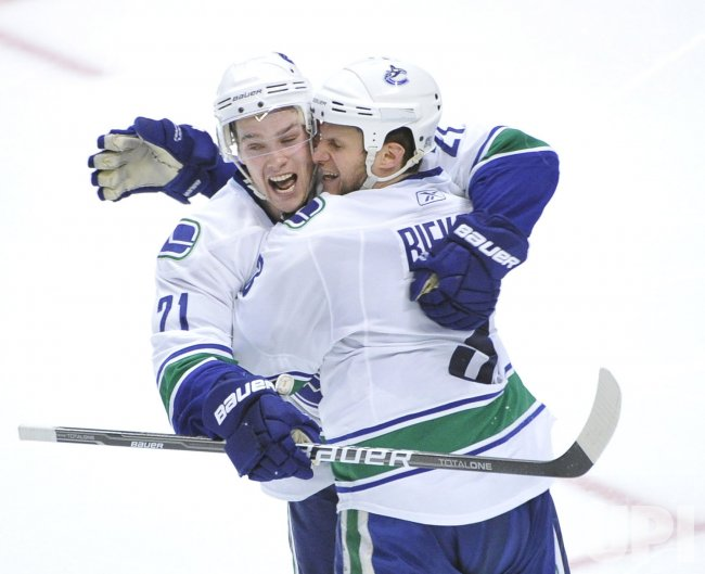 Canucks Raymond and Bieksa celebrate goal against Blackhawks in Chicago
