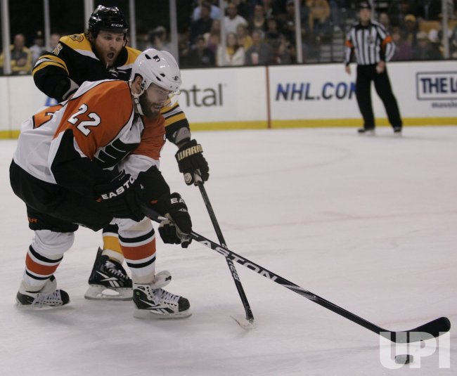 Flyers Leino skates around Bruins Wideman in Game 5 of the NHL Eastern Conference Semi-Final in Boston, MA.