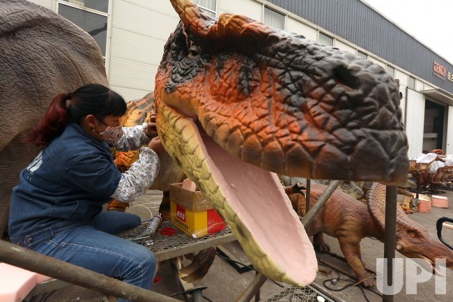 A Chinese worker puts the finishing touches on a robotic dinosaur in Zigong, China