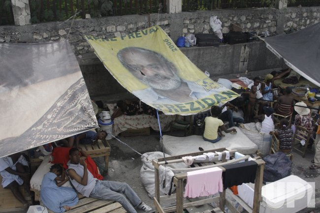 People use a giant portrait of Haiti's President Rene Preval to cover themselves