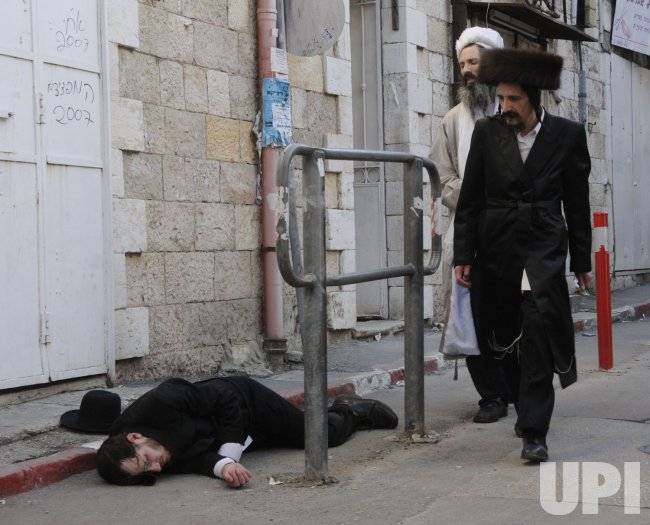 An Ultra-Orthodox Jew lays on the street after becoming inebriated during the Purim celebration in Jerusalem