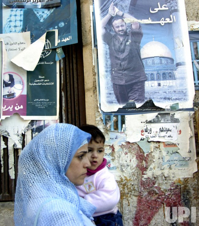 PALESTINIANS WALK BY A POSTER OF MARWAN BARGHOUTI IN RAMALLAH