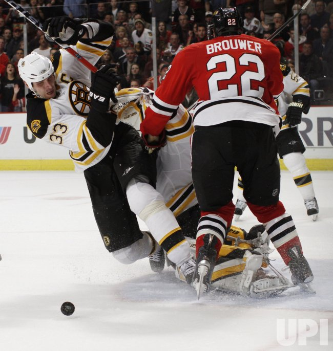 Bruins Chara Thomas and Blackhawks Brouwer collide at net in Chicago