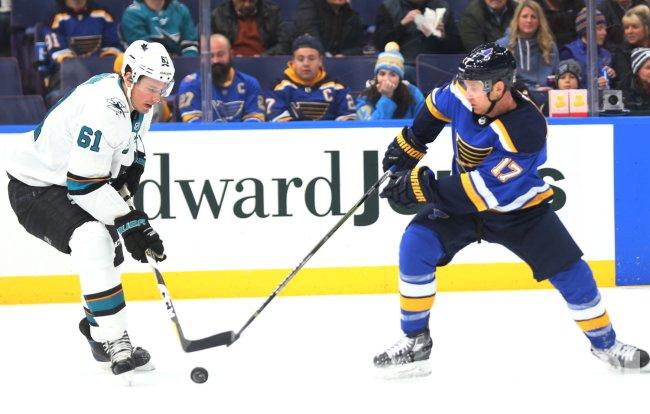 San Jose Sharks Justin Brown battles St. Louis Blues Jaden Schwartz for control of the puck