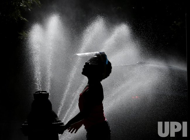 A Child Wears a Face Shield Playing in an Open Hydrant in New York