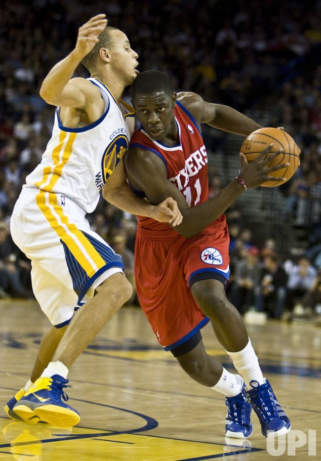 Philadelphia 76ers Jrue Holiday drives on Golden State Warriors Stephen Curry in Oakland, California