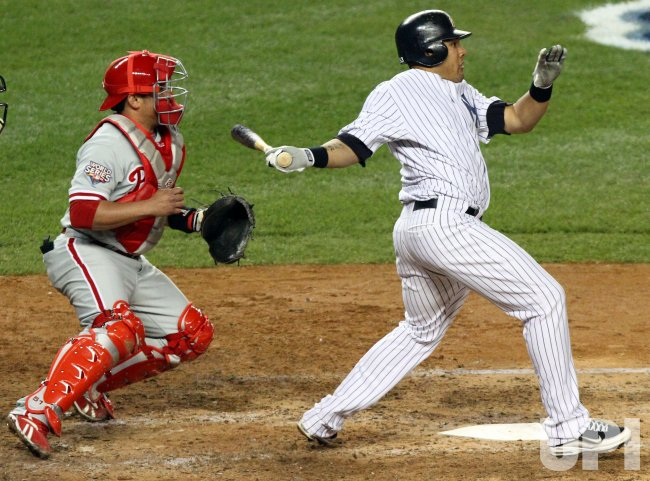 Philadelphia Phillies Carlos Ruiz watches as New York Yankees Melky Cabrera hits a single in the seventh inning in game 2 of the World Series at Yankee Stadium in New York