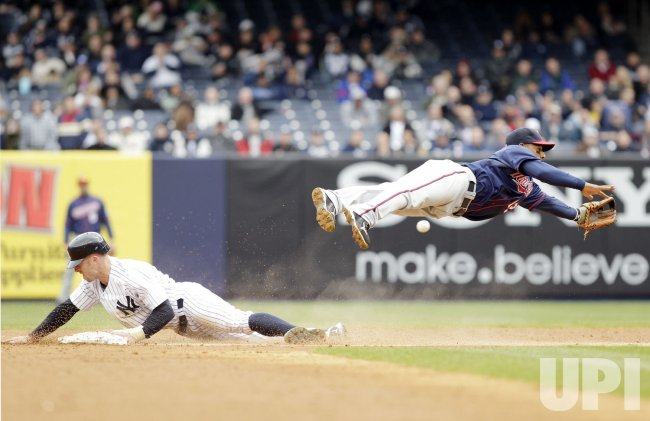 New York Yankees Brett Gardner slides under Minnesota Twins Alexi Casilla at Yankee Stadium in New York