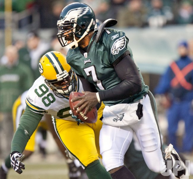 Philadelphia Eagles quarterback Michael Vick evades a tackle by Green Bay C. J. Wilson.