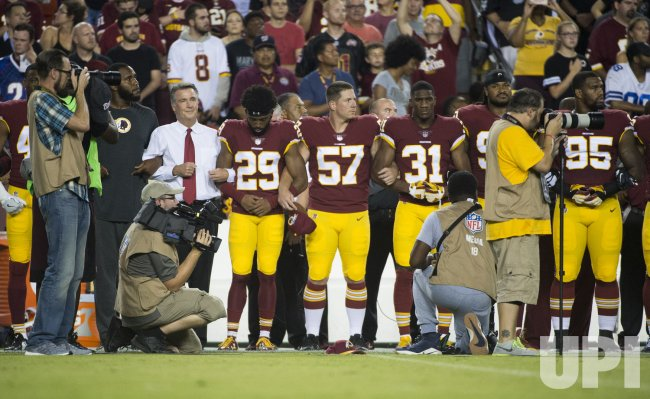 Members of the Washington Redskins Link Arms during the National Anthem