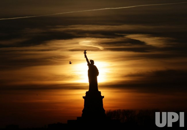 Sunset Behind the Statue Of Liberty in New York