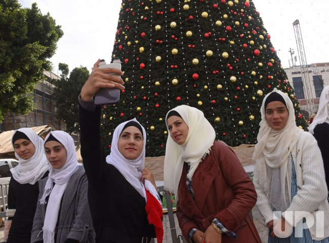 Palestinians Take A Selfie In Front Of A Christmas Tree In Bethlehem, West Bank