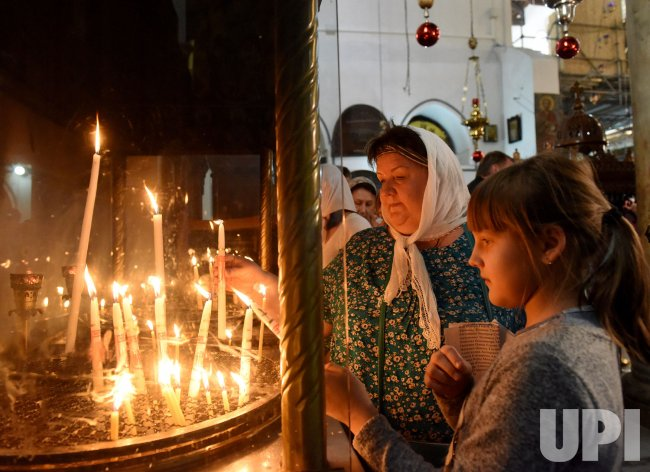 Russian Tourists Light Candles In The Church Of Nativity In Bethlehem, West Bank