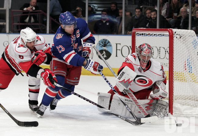 Carolina Hurricanes Tim Gleason tries to prevent New York Rangers Chris Drury (23) from getting the puck by Cam Ward at Madison Square Garden in New York