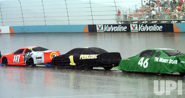 The cars of #10 Ricky Rudd, #1 Steve Park, and #46 Jeff Green are covered in a heavy rain storm