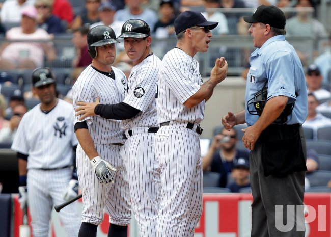 New York Yankees Rob Thomson holds back Brett Gardner while manager Joe Girardi argues with home plate umpire Paul Emmel at Yankee Stadium in New York