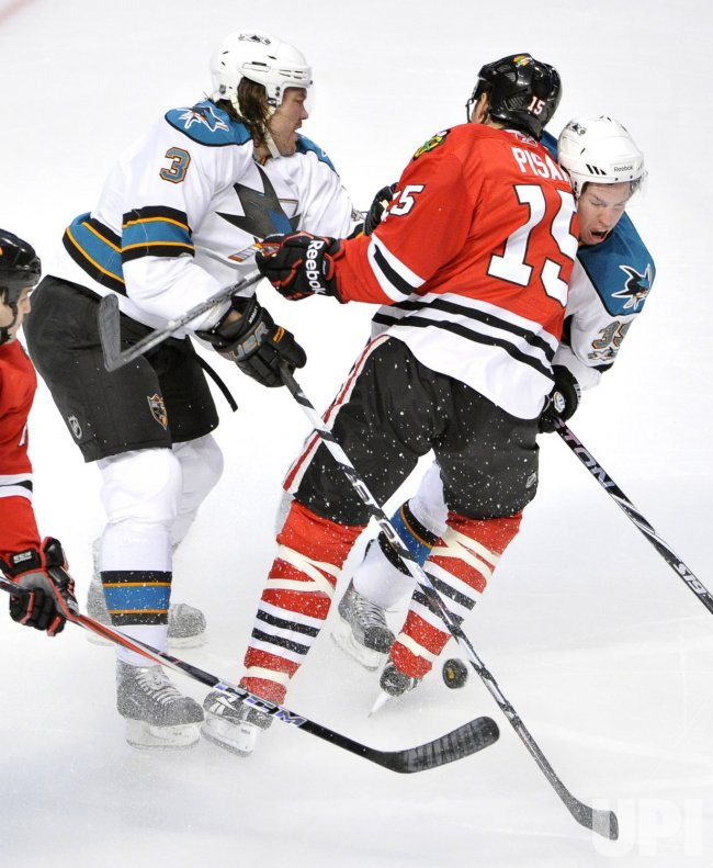 Sharks Murray, checks Blackhawks Pisani in Chicago