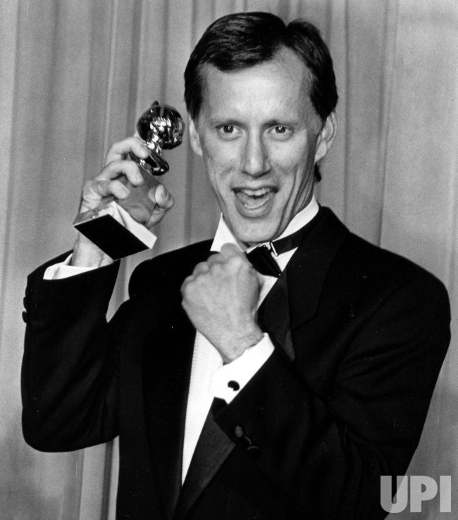 Actor James Woods holds up the Golden Globe award.