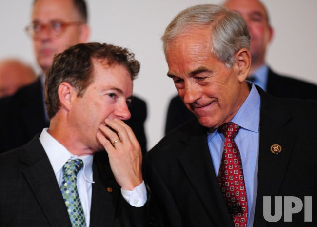 Rep. Ron Paul (R-TX) (R) talks to Sen. Rand Paul (R-KY) in Washington