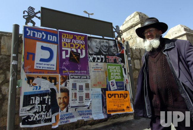 AN ISRAELI WALKS BY ELECTION POSTERS IN JERUSALEM
