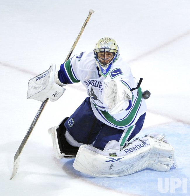 Canucks goalie Luongo reaches for puck against Blackhawks in Chicago