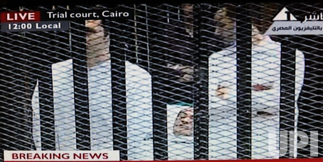 Video image of former Egyptian leader Hosni Mubarak in a cage in a Cairo courtroom