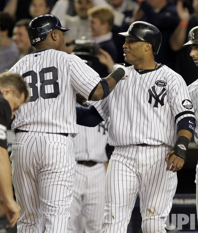 New York Yankees Marcus Thames and Robinson Cano react in Game 3 of the 2010 ALDS at Yankee Stadium in New York