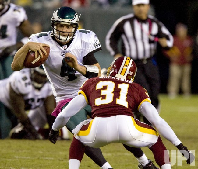 Philadellphia Eagles quarterback Kevin Kolb gains yardage around Washington Redskins cornerback Phillip Buchanon