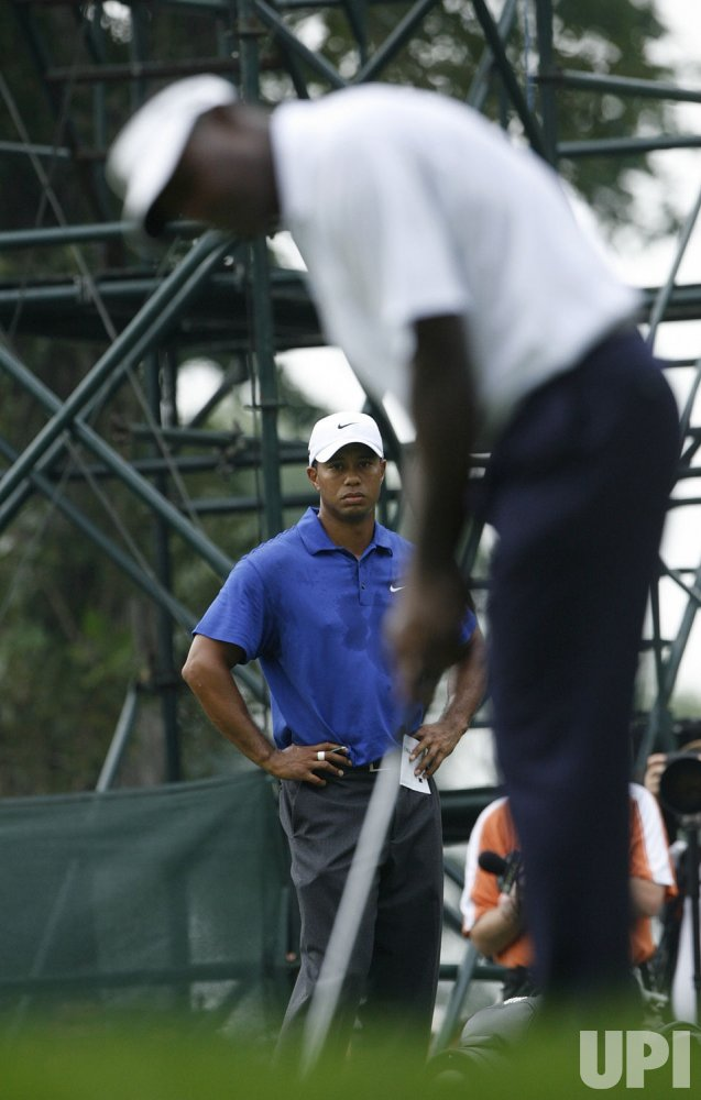 Tiger Woods watches Vijay Singh putt on the third hole during the third round of the 91st PGA Championship in Chaska, Minnesota
