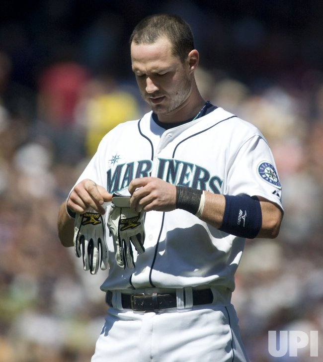 Seattle Mariners' Jack Hannahan puts away his batting gloves after grounding out to New York Yankees first baseman Nick Swisher in the second inning at SAFECO Field in Seattle.