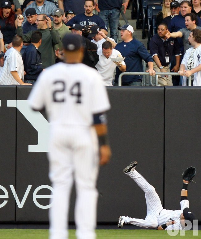 New York Yankees Nick Swisher looks in his glove while fans react at Yankee Stadium in New York