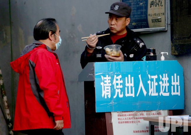 A Chinese security guard eats without a face mask in Beijing, China