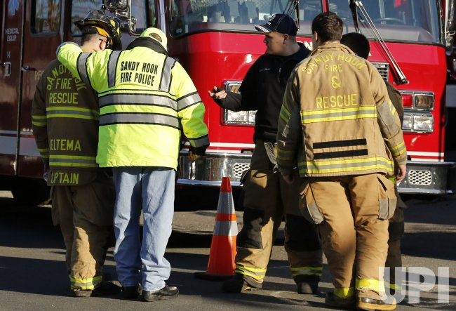 Firefighters console one another outside Sandy Hook Elementary School following shooting in Newtown, CT.