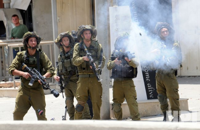 """Israeli soldiers fire tear gas at stone throwing Palestinians during clashes on the 63rd anniversary of """"Nakba"""" in Qalandiya, West Bank"""