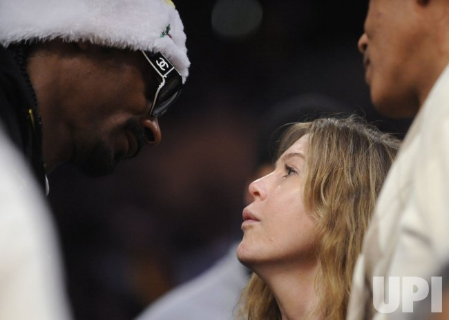 Recording artist Snoop Dogg and actress Ellen Pompeo talk at an NBA basketball game between the Los Angeles Lakers and the Cleveland Cavaliers in Los Angeles