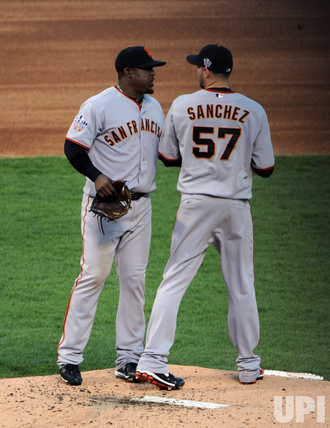 Giants' Juan Uribe talks with pitcher Jonathan Sanchez during the first inning of game 3 of the World Series