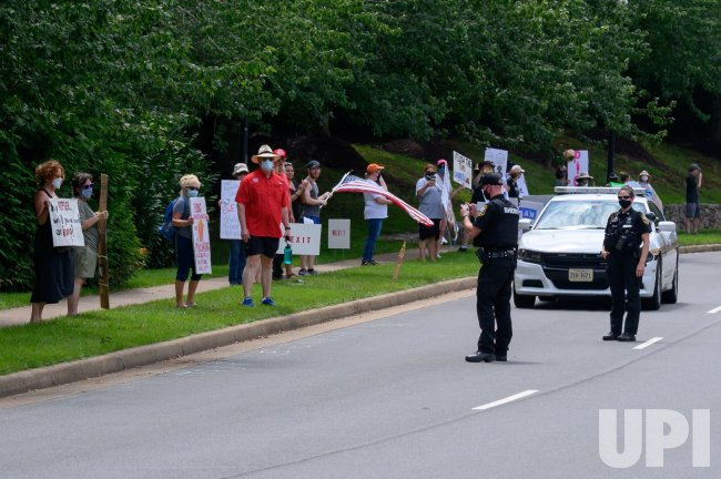 Protesters hold signs outside the Trump National Golf Club