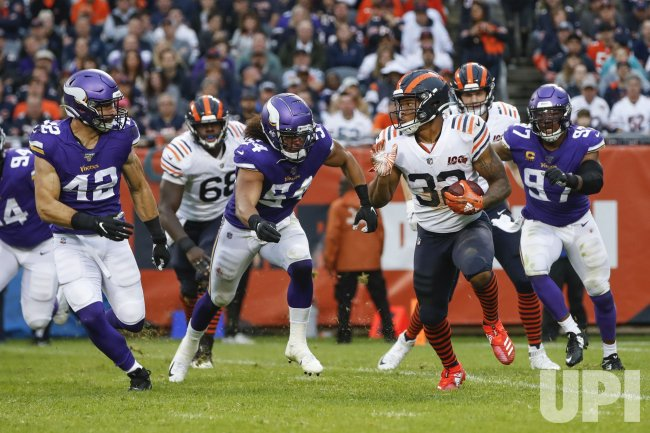 Bears David Montgomery is defended by Minnesota Vikings in Chicago