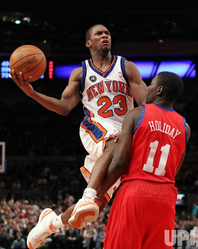 New York Knicks Toney Douglas drives by Philadelphia 76ers Jrue Holiday at Madison Square Garden