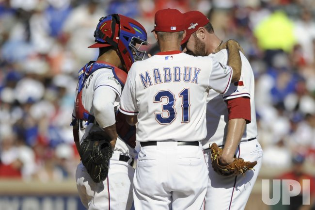 Texas Rangers' catcher Robinson Chirinos and pitching coach Mike Maddux visit pitcher Colby Lewis