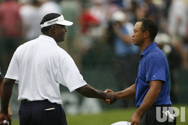 Tiger Woods (R) and Vijay Singh shake hands after the third round of the 91st PGA Championship in Chaska, Minnesota
