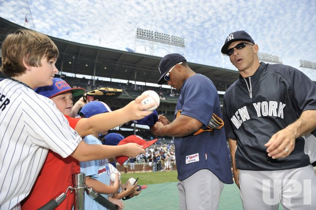 Yankees' Cano signs autographs as Girardi walks by in Chicago