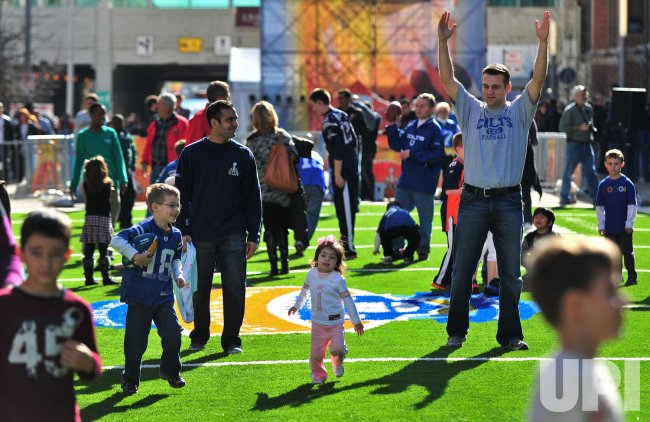 Fans pose for a football in the Fan Zone area in Indianapolis