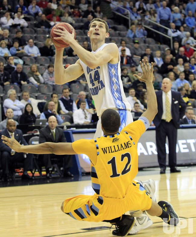 North Carolina Tar Heels Tyler Zeller knocks over Marquette Golden Eagles Erik Williams at the NCAA Final Four East Regional Round at the Prudential Center in New Jersey