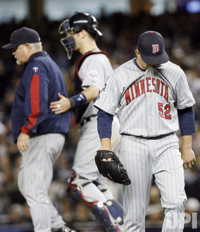 Minnesota Twins starting pitcher Brian Duensing bites his shirt after beng taken out of the game while Joe Mauer puts his arm around manager Ron Gardenhire against the New York Yankees in game 1 of the ALDS at Yankee Stadium in New York