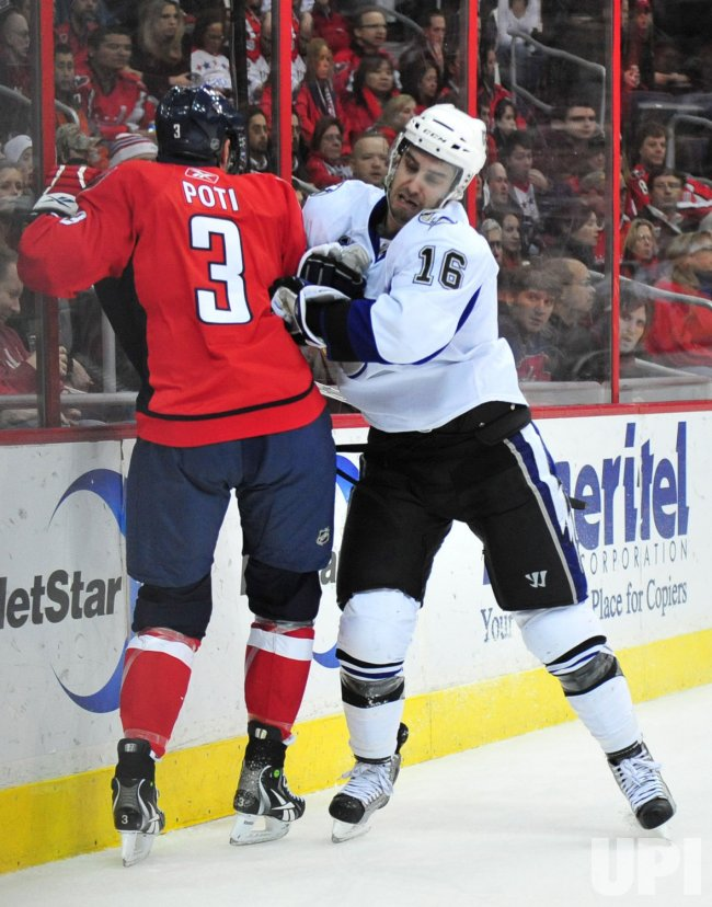 Tampa Bay Lightning' Teddy Purcell puts Washington Capitals' Tom Poti in Washington