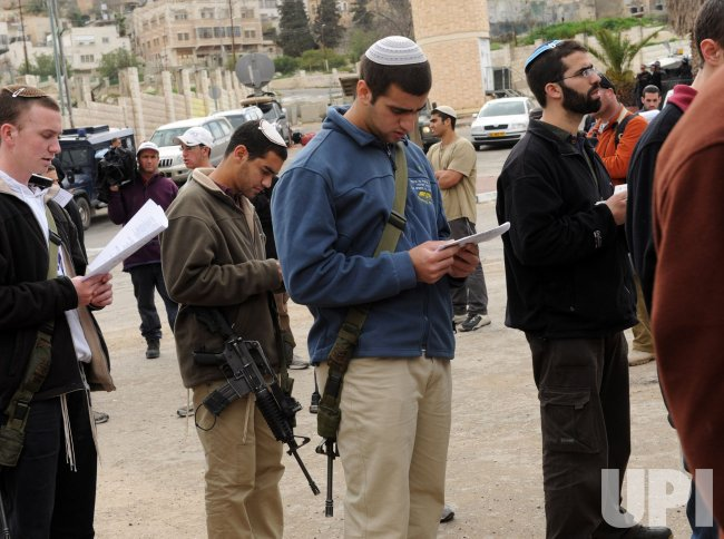 Israeli settlers carry automatic weapons at a pray and